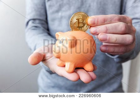 Piggy Bank, Hand Holds Golden Bitcoin Coin Virtual Money. Cryptocurrency And Saving Concept
