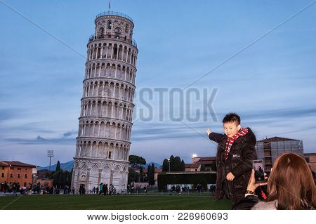 Pisa, Italy - February 11, 2018: Asian Child Poses For A Picture With The Famous Tower Of Pisa In Th