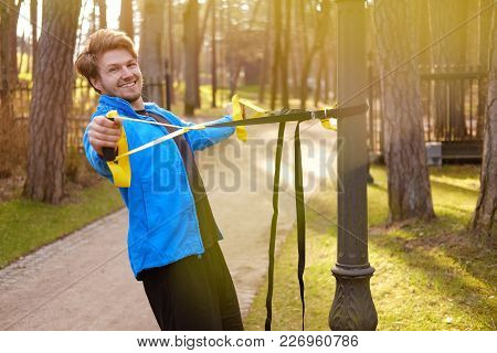 Attractive Sporty Male Exercising With Fitness Trx Strips In A Park.