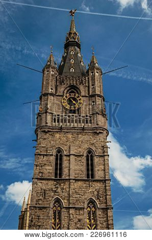 Top Of Stone Gothic Tower With Golden Clock And Blue Sky In Ghent. In Addition To Intense Cultural L