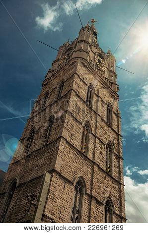 Stone Gothic Tower With Golden Clock And Shinny Sky In Ghent. In Addition To Intense Cultural Life,