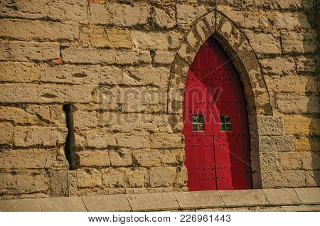 Red Wooden Door In Gothic Style In The City Center Of Ghent. In Addition To Intense Cultural Life, T