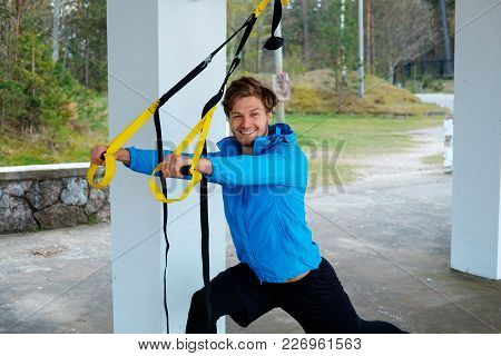 Smiling Sporty Man In A Blue Jacket Exercising With Fitness Trx Strips.