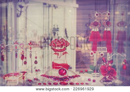 Red Jewelry At Showcase Of Store. Counter With Variety Jewelry In Store Window In Shopping Mall.