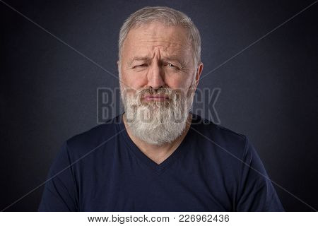 A 60 Year Old Man With Gray Beard Posing Spoiled Grimace In The Studio
