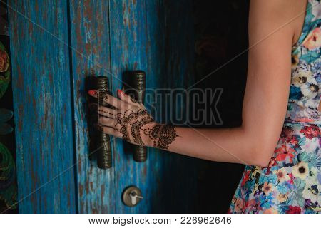 Female Hand With Henna Tattoo Touching Antique Blue Door. Beautiful Indian Mehendi Ornaments Painted
