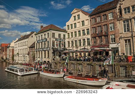 Ghent, Belgium - July 03, 2017. Old Buildings In Front Of The Canal, With Boats And People In Ghent.
