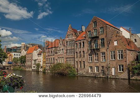 Old Buildings In Front Of The Canal With Blue Sky In The City Center Of Ghent. In Addition To Intens