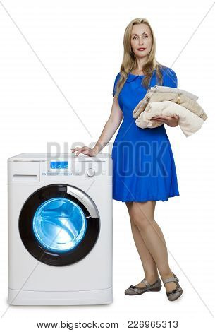 happy young woman in a blue dress near the new washing machine