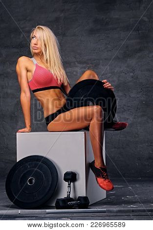 Full Body Studio Portrait Of Sensual Sporty Blond Female Sits On A White Wooden Box And Holds Barbel