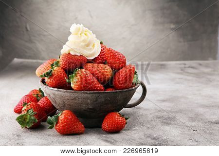 Fresh Strawberries And Whipped Cream On Grey Vintage Bowl.