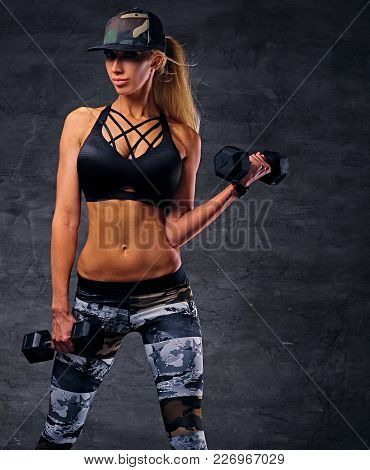Sexy Female Fitness Model Dressed In A Black Sportswear And Camouflage Baseball Cap Holds Dumbbells.