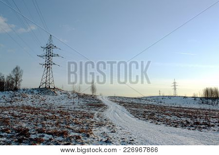 Power Transmission Line On A Hill In The Background Of A Clear Evening Sky And Winter Road With Trac