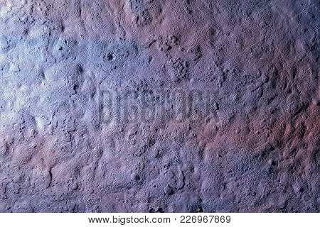 Old Rough Surface Of A Concrete Wall With An Uneven Coating Of Purple Colored Paint