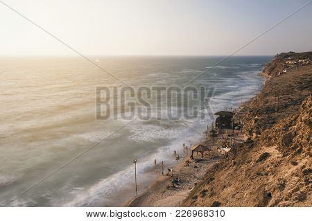Summer View Of Israeli Crowded Beach Shoreline From Above With Sunset At The Background, Israel