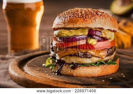 Appetizing Cheeseburger, Made From Sesame Seeds Sprinkled Rye Bun With Tomato Slice And Melted Chees