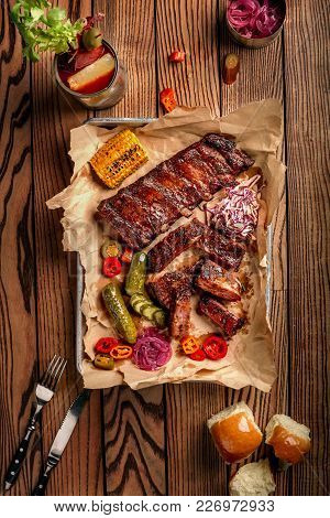 Grilled Pork Ribs Served With Grilled Corn, Salat, Bbq Sauce, Salt Pepper And Cucumber On Parchment
