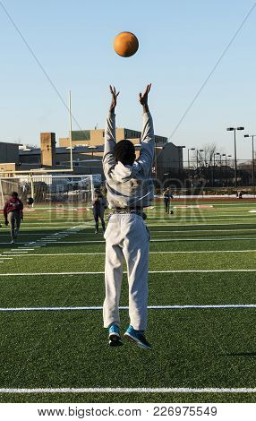 A Male High School Track And Field Athlete Throwing A Medicine Ball In The Air And Jumping Off Of Th
