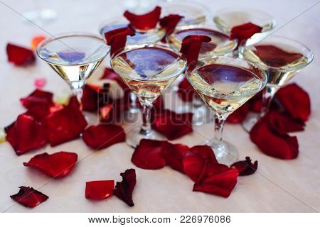 Glasses Of Martini And Champagne On A Festive Wedding Table Decorated With Rose Petals