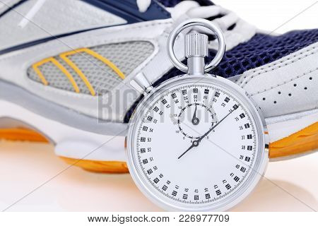 Analogue Stopwatch With Sport Running Shoes On White Background
