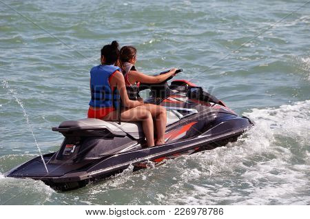 Two Young Women Riding Tandem On A Jet Ski.