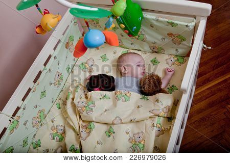 New Born Child In Wooden Co-sleeper Crib. Infant Sleeping In Bedside Bassinet. Safe Co-sleeping In A