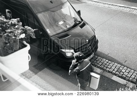 Paris, France - Feb 16, 2018: Courier Enters Ups United Parcel Service Brown Delivery Van With Cardb