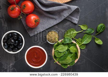 Italian Cuisine. Mediterranean Cuisine. Tomato, Spinach Leaves, Oregano, Tomato Sauce And Olives On