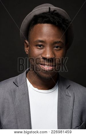 Portrait Of A Fashionable African American Man Smiling On Black Background. A Nice Guy In A Gray Jac