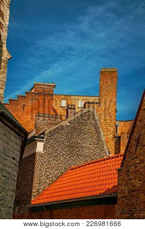 Close-up Of Brick Walls And Roofs Against Blue Sunny Sky. With Many Canals And Old Buildings, This G