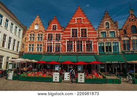 Bruges, Belgium - July 05, 2017. Building And Eateries At The Market Square In Bruges. With Many Can