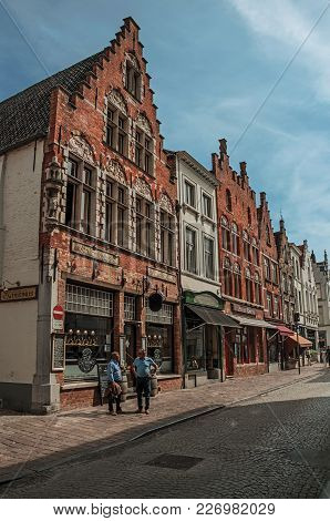 Bruges, Belgium - July 05, 2017. Brick Building, Shops And People In Street Of Bruges. With Many Can