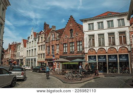 Bruges, Belgium - July 05, 2017. Street With People, Brick Houses And Shops At Bruges. With Many Can