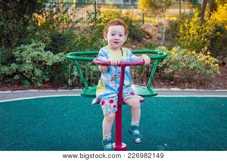 Redhead Toddler Girl Smiling From The Carousel At Sunset