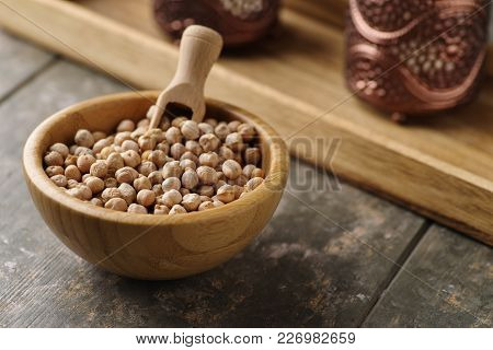 Dried Chickpeas In A Small Bowl On A Rustic Wooden Background.