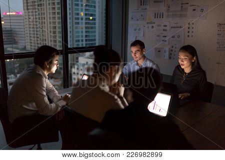 Business People Team Working Late Night In Low Light From Laptop Screen With Cityscape Blurred Backg