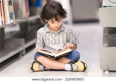 Smart Boy With Many Book Sitting On Floor. Happy Children Learning Class In Library. Development Of