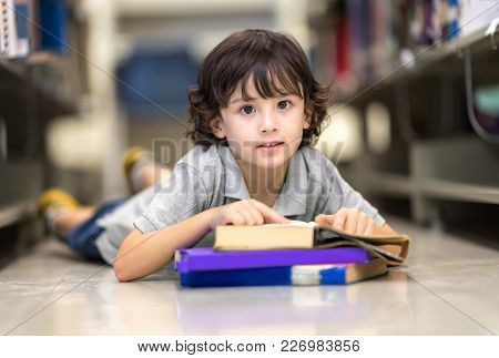 Smart Boy With Many Book Sleeping On Floor. Happy Children Learning Class In Library. Development Of
