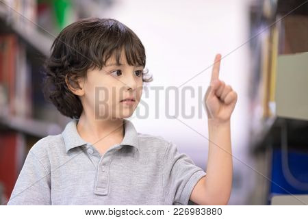 Cute Boy Showing Forefinger As Pressing Touchscreen In The Air. Education Concept. Setup Studio Shoo