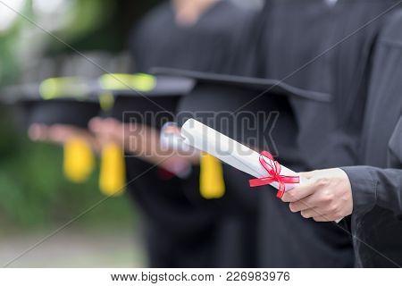 In Selective Focus Of A Certificate In Hand, Congratulation Graduation Day, Row Of Happily Graduates