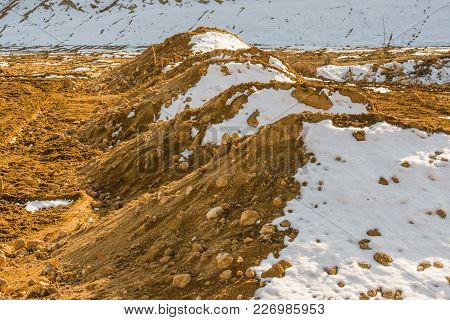 Rural Winter Landscape Of Four Dirt Mounds Partially Covered With Snow With Snow Covered Hillside In