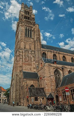 Bruges, Belgium - July 05, 2017. Church Tower, People And Bikes On A Street Of Bruges. With Many Can