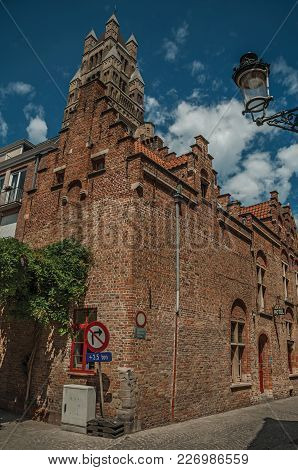 Brick Facade Of An Old Building And Tower, On A Street Corner Of Bruges. With Many Canals And Old Bu