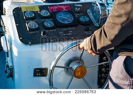 Boat Instrument Panel, With A Caucasian Man With Hands On The Steering Wheel.