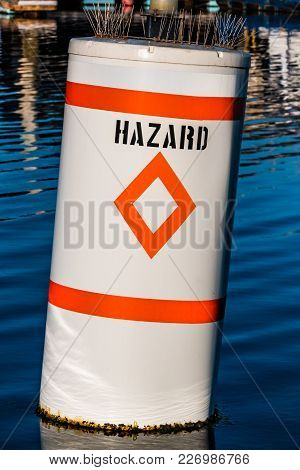 Diamond Hazard Warning Buoy In Body Of Water With Bird Spikes.