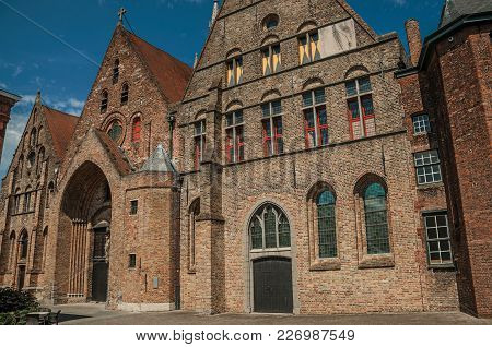 Brick Facade Of Church, Wooden Door And Blue Sky In An Alleyway Of Bruges. With Many Canals And Old