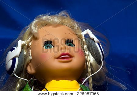 Doll With Headphones, A Music Lover, An Artificial World.