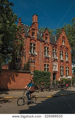 Bruges, Belgium - July 05, 2017. Brick Building And Woman Riding A Bicycle In Bruges. With Many Cana
