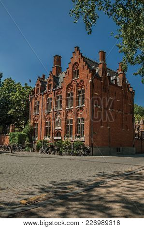 Bruges, Northwestern Belgium - July 05, 2017. Brick Facade Of Old House, Trees And Bicycles In Bruge