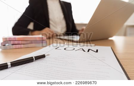 Selective Focus Pen On Business Loan Application Form With Banker In Background. Business Loan, Pers